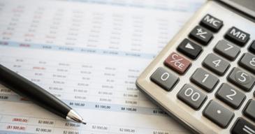 Calculadora y lapicera junto a un presupuesto que armo la consultora de recursos humanos mostrando como ahorrar costos en tu empresa