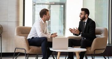 Dos hombres de traje y camisa conversando sobre los procesos de headhunting para empresas