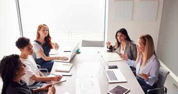 Grupo de mujeres profesionales debatiendo como delegar la toma de decisiones en su empresa