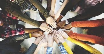 Manos unidas de los colaboradores de una empresa simbolizando multiculturalidad y diversidad