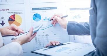 Manos y brazos de profesionales calculando los costos de la gestión de recursos humanos